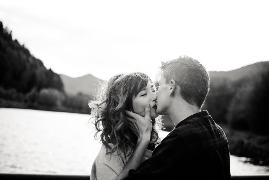 A black and white picture of two people kissing with a lake in the background.