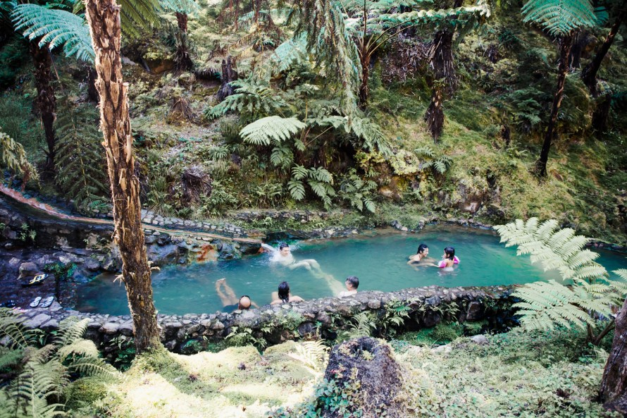 People in forested hot springs pool