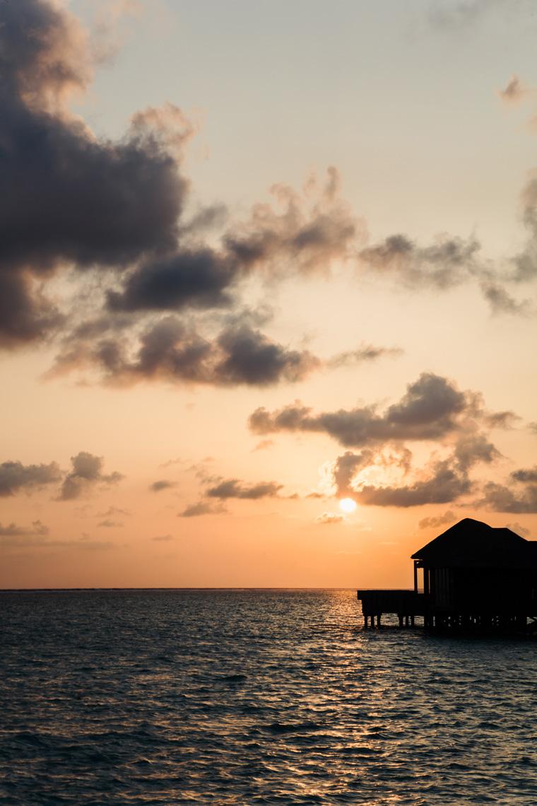Sun setting behind overwater villas