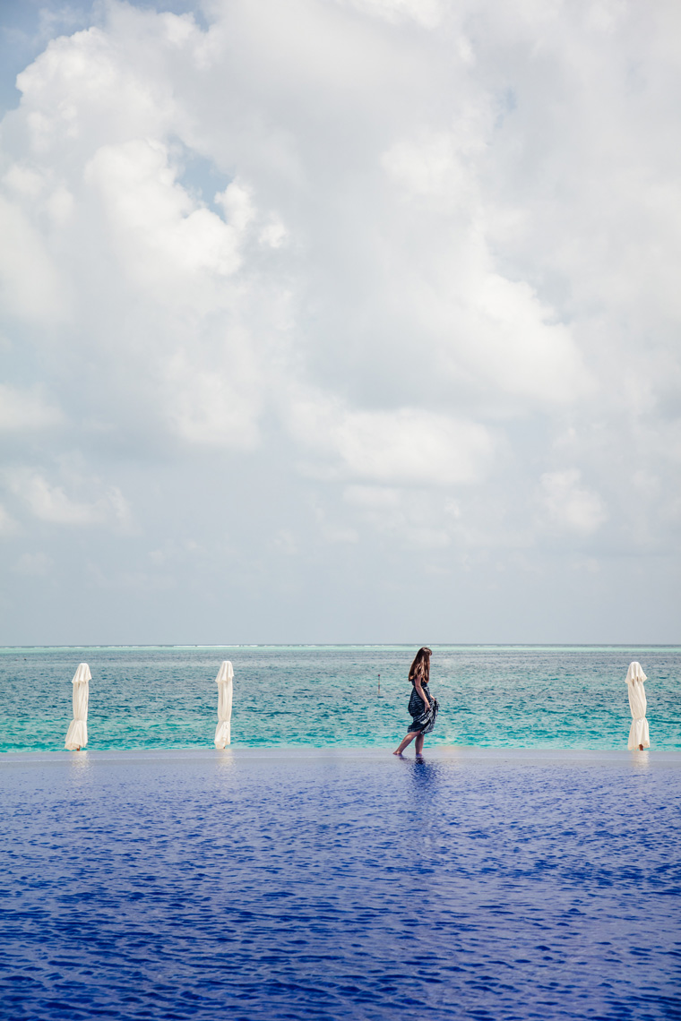 Carly walking by infinity pool