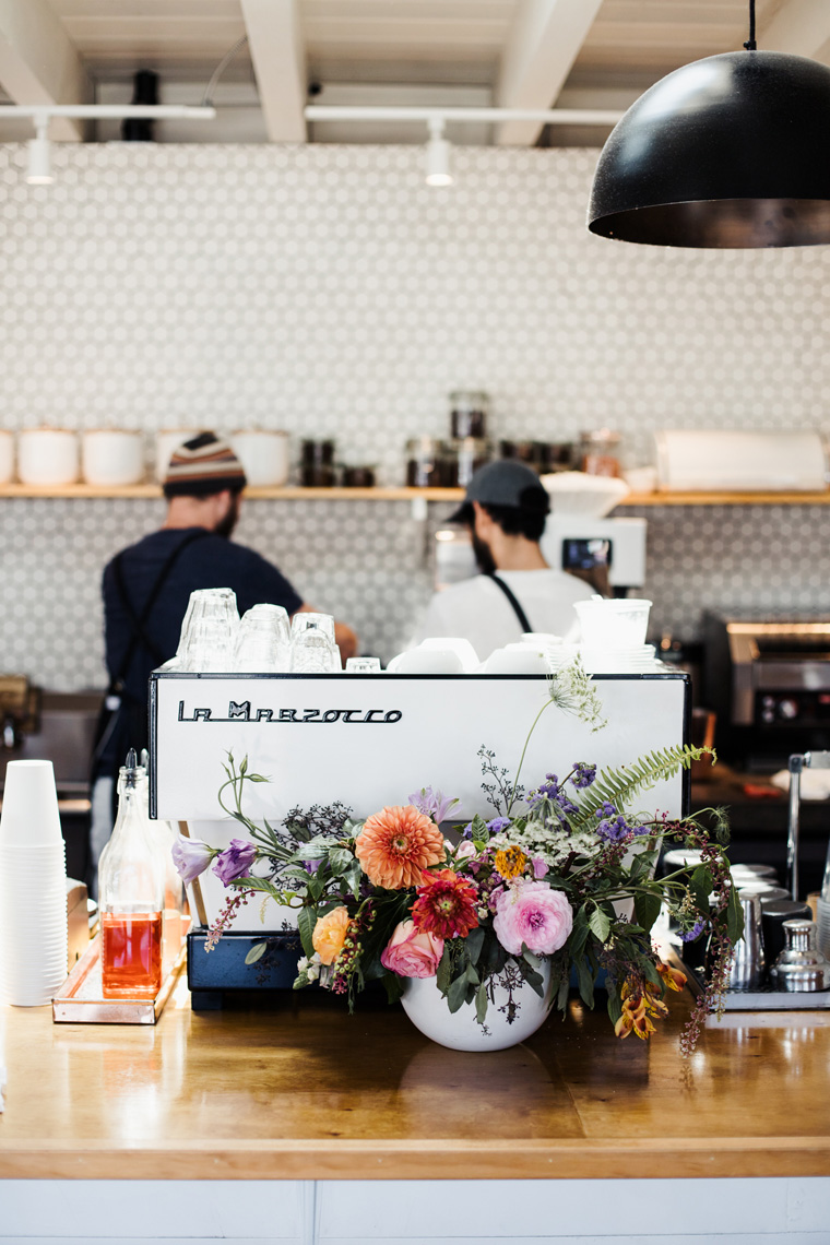 Flowers in front of two men making coffee
