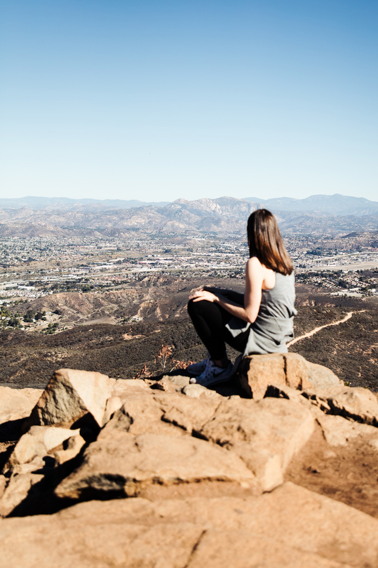 Carly sitting on rock overlooking mountains