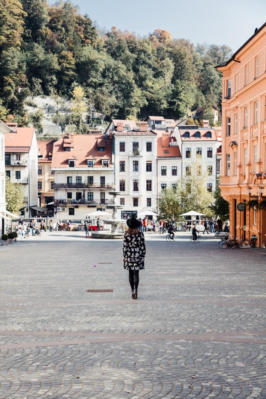 Carly walking down cobblestone street in Ljubljana