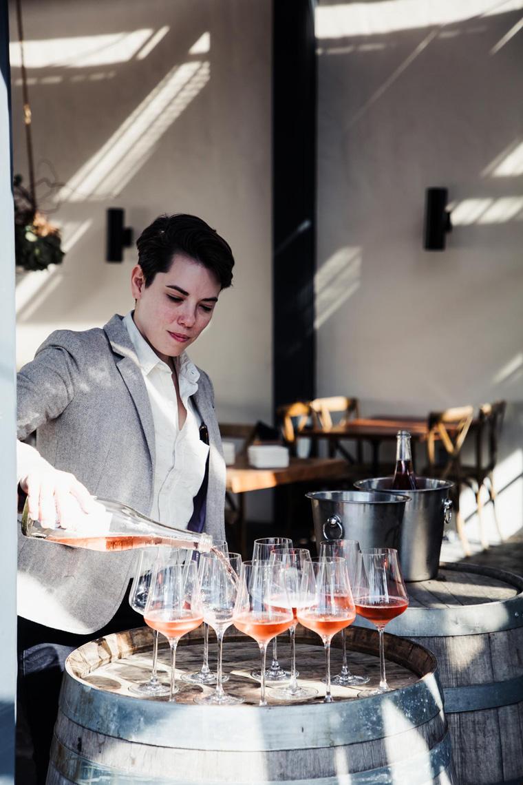 Person pouring wine glasses