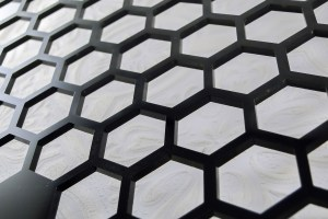 The template itself is just a rectangle of material with a hex pattern cut out.