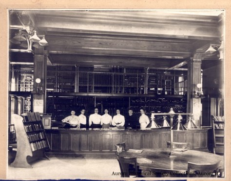 The is the inside of the 1904 library, open stacks visible behind the desk.  Photo from the Collection of the Aurora Historical Society