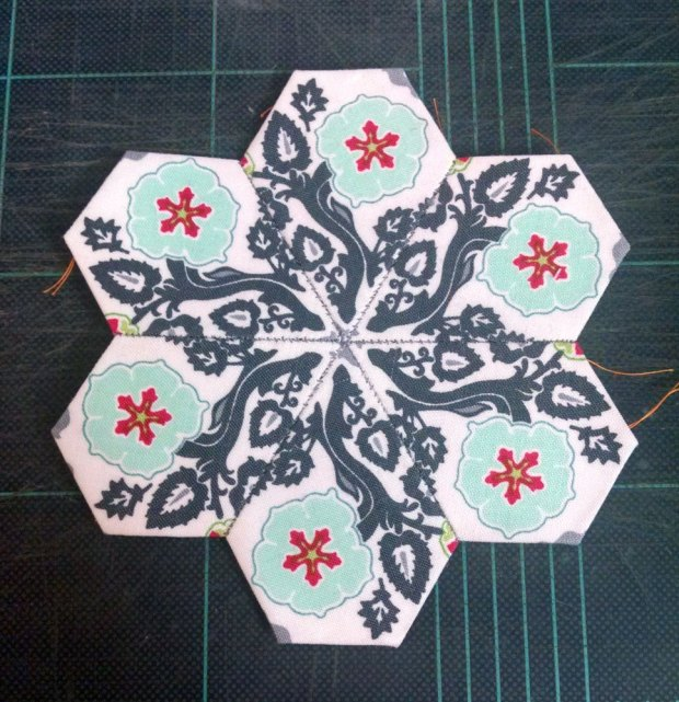 Here's my version - my first fussy cut bloom!  The 6 jewels with the same pattern are sewn points in to make this star, which has a kaleidoscope kind of feel to it.