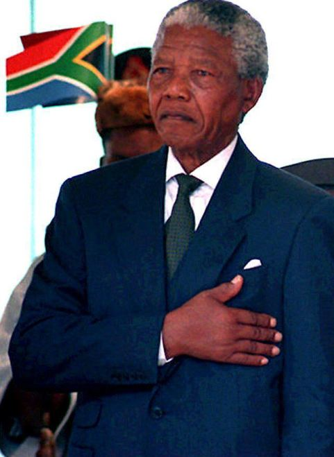 PRETORIA, SOUTH AFRICA: South African President Nelson Mandela stands at attention as the national anthem is played during his inauguration 10 May 1994 at the Union Buildings in Pretoria. Mandela is South Africa's first democratically elected president, having been elected in the country's first all-race elections. (Photo credit should read WALTER DHLADHLA/AFP/Getty Images)