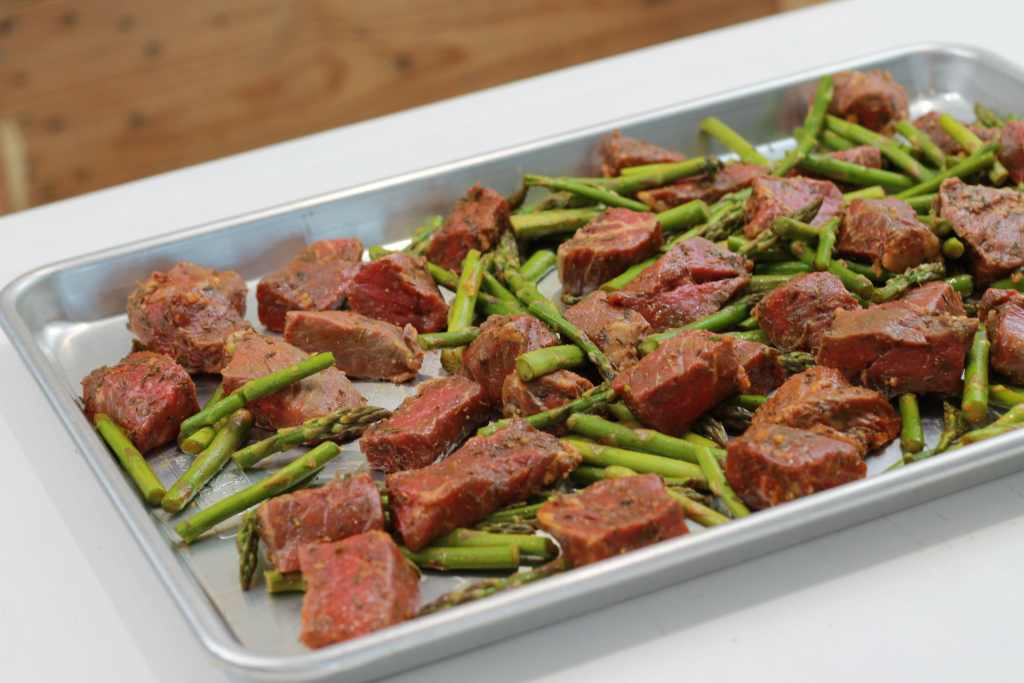 From fridge to table this ONE PAN Spicy Steak Bites and asparagus recipe is easily spread onto a baking pan and dinner will be ready in under 15 minutes. YUM! We can actually have steak on a weeknight now. | 5dinners1hour.com