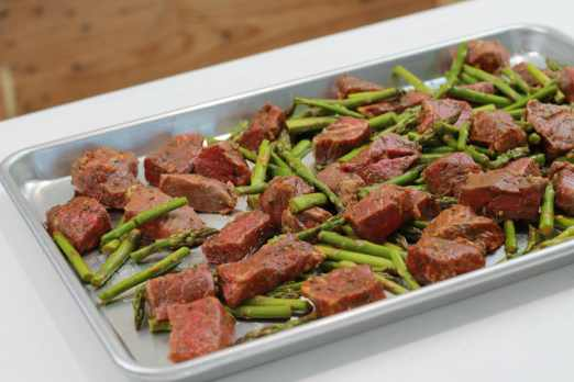 Sheet pan with spicey steak bites and asparagus ready to be broiled.