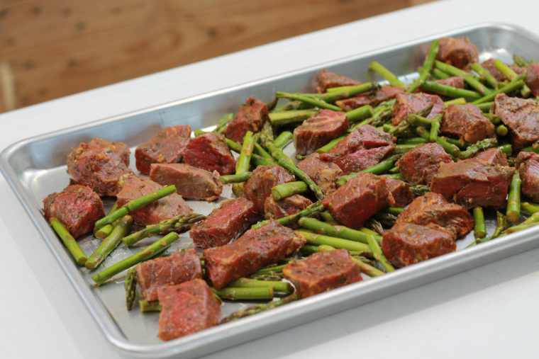 Sheet pan with spicey steak bites and asparagus ready to be broiled on a pan.