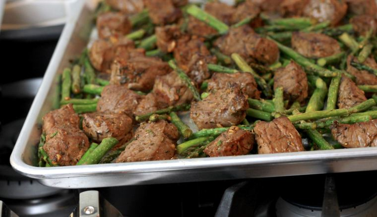 Sheet pan with broiled spicey steak bites and asparagus.