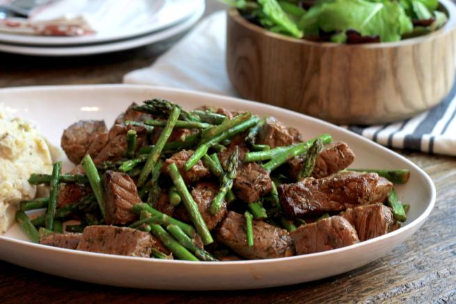 Broiled steak bites with asparagus and mashed potatoes served on an oval plate.