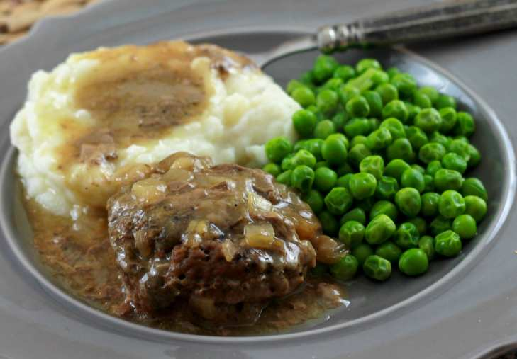 salisbury steak with brown gravy on a white plate served with mash potatoes and green beans.