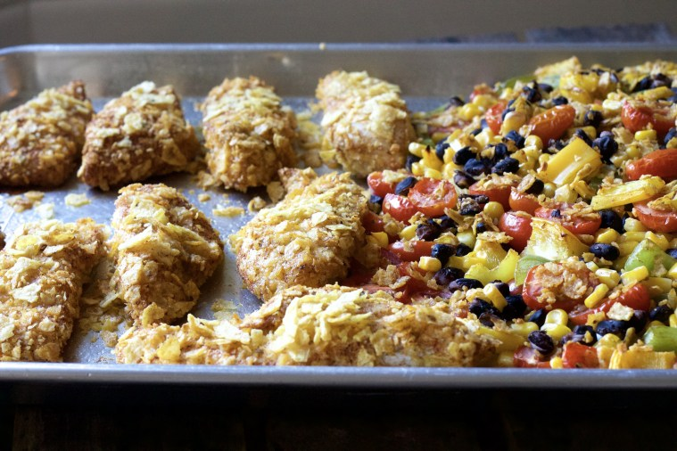 baked crispy tortilla chicken strips on a sheet pan with black bean, corn and tomato side.