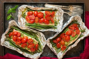 three foil packages of roasted cherry tomatoes and asparagus on a serving tray.