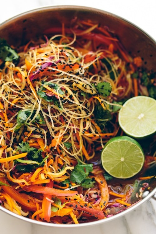 Pasta with glass noodles, lime slices, cilantro, and sliced carrots in a bowl.