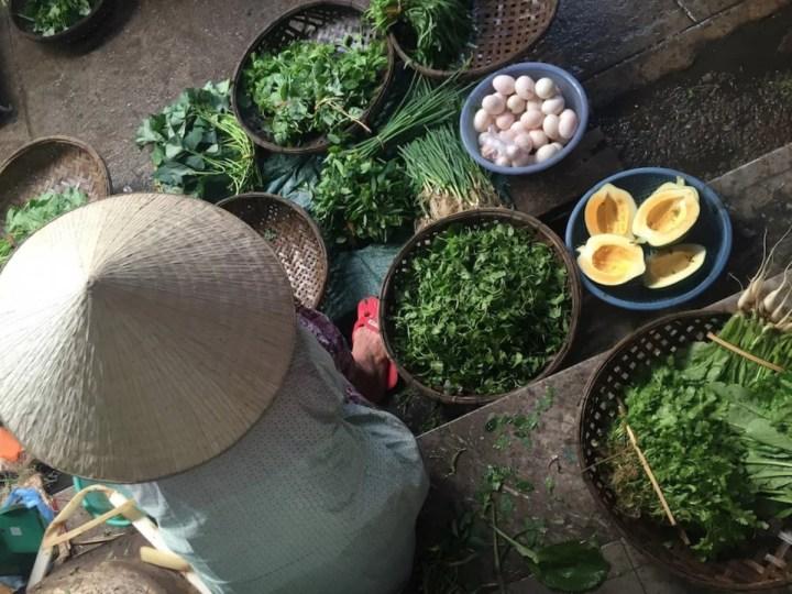 kvinde der sælger grøntsager på marked