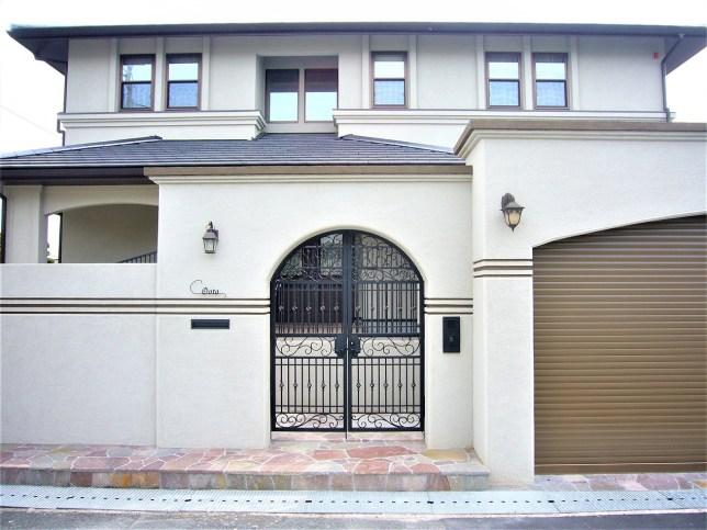 ゲートのある白と茶色の外構
