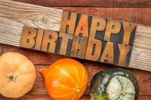 46066162 - happy birthday greeting card - text in letterpress wood type printing blocks over rustic grained barn wood with winter squash