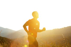 Silhouette of a man running outdoors with sunsetting behind him