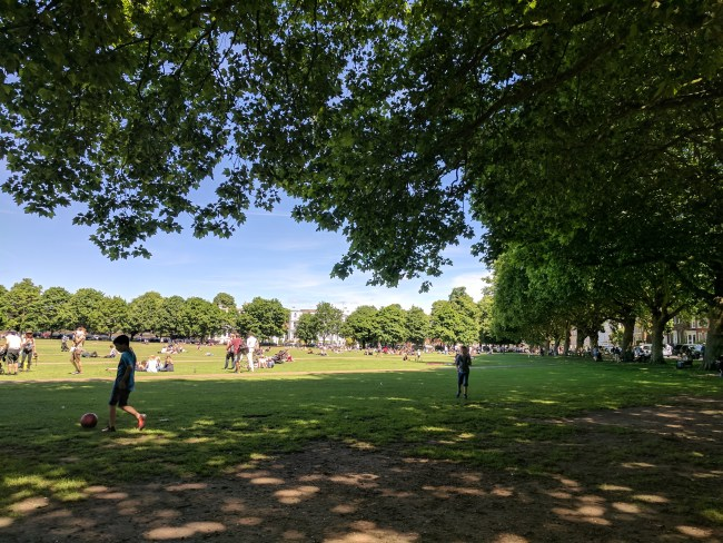 Sit in the shade on a bench watching the people pass by on Richmond Green. Today the green was busy with cricket being played and people enjoying the sun.