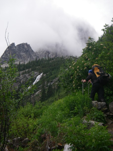 """Thursday: About half-way along the hike into/up to the Bugaboos, we get our first look at the famous Conrad Kain Hut (the green roof at the top of the wall above the waterfall). Almost there...but from here on up the trail gets a little more """"interesting""""..... How DO we get up that wall the hut's sitting on?"""