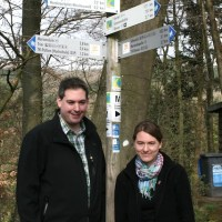 Thomas Kalff und Liane Jordan vor einem Wegweiser des neuen Wanderwegs