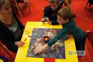 Eine Mutter spielt mit zwei Kindern Feuerdrachen auf der SPIEL 2014.