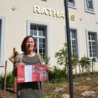 Bürgermeisterin Elvira Garbes präsentiert den Info-Flyer für die Solidarkarte vor dem Trierer Rathaus. Foto: Presseamt Trier