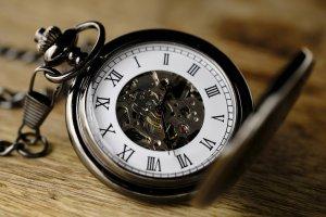 Alte rustikale Taschenuhr liegt auf einem Tisch.