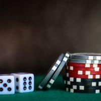 Foto zeigt 2 Würfen und Pokerchips auf einem Tisch. - Foto: Heather Gill / unsplash.com