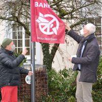 OB Wolfram Leibe (r.) hisst mit Unterstützung von Alois Barra die Flagge der Internationalen Kampagne zum Verbot von Atomwaffen (ICAN) vor dem Rathaus. Bildquelle: Presseamt Trier