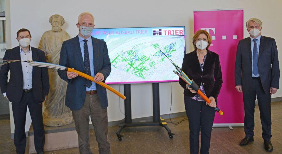 Ministerpräsidentin Malu Dreyer und OB Wolfram Leibe sowie Michael Löttner (l.) und Thomas Müller (r.) von der Telekom stellen das Glasfaserprojekt vor. Die Karte im Hintergrund zeigt die Teile von Trier-Nord, in denen die digitale Infrastruktur in den nächsten Monaten aufgewertet wird. Bildquelle: Presseamt Trier