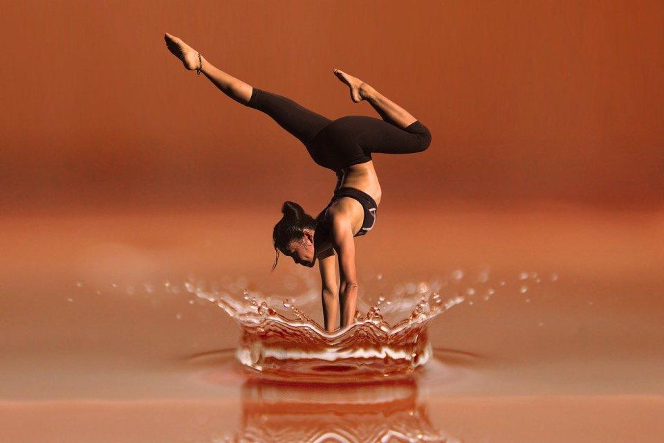 Eine Tänzerin macht einen künstlerischen Handstand in einer Wasserlache. Foto: Bild von Gerd Altmann auf Pixabay