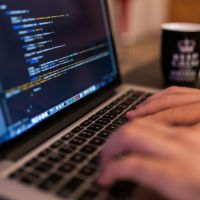 Das Bild zeigt zwei Hände, die auf einem Macbook programmieren. Foto: Bild von Free-Photos auf Pixabay