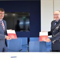 Prof. Dr. Michael Jäckel, Präsident der Universität Trier, und Friedel Durben, Direktor der Hochschule der Polizei Rheinland-Pfalz, bei der Unterzeichnung des Kooperationsabkommens. Bildquelle: Universität Trier