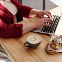 Eine Frau im Rollstuhl arbeitet im Homeoffice an einem Notebook auf dem Küchentisch. Nebenan steht eine Tasse Kaffee und ein gesundes gut belegtes Brot. - Foto: Pexels - by marcus-aurelius