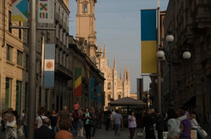 View along a shopping street in Milan with a view at the cathedral. The flags advertise for the upcoming World Expo 2015.
