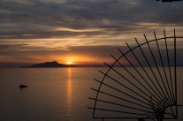 The sun sets over the island Ischia, lighting up the sky