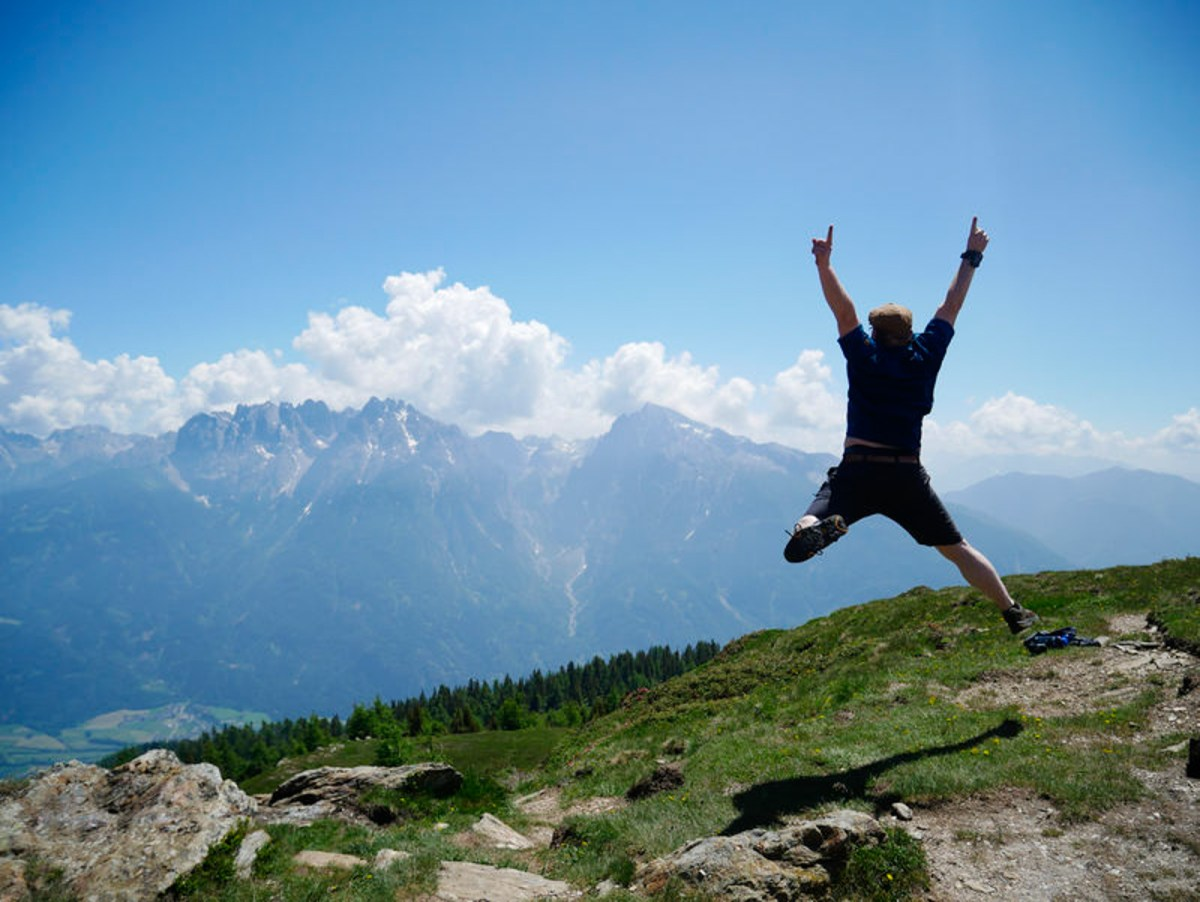 Man jumps in front of a mountain panorama in the Austrian Dolomites