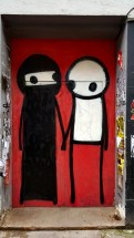 Two stick figures by street artist STIK in London, one showing a woman in a hidschab.