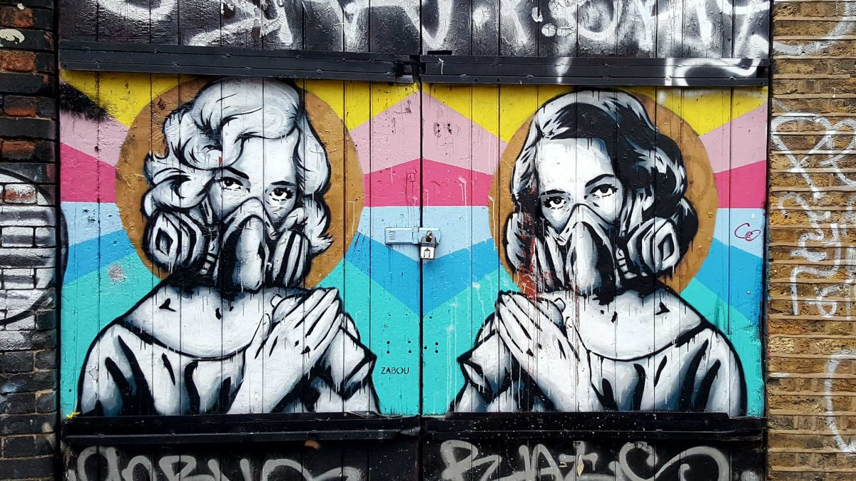 Urban art by zabou showing two women with gasmasks on a wooden door in Shoreditch, London