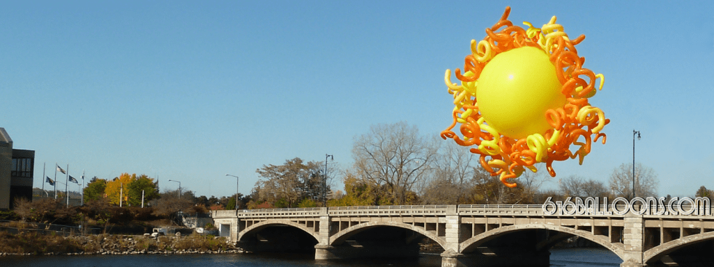 Giant 3' yellow balloon sun and the lovely Pearl St. Bridge and beautiful blue Grand Rapids, Mi sky in the background. 616Balloons.com Grand Rapids, Michigan. Specializing in high end balloon art & decor for the best corporate or private parties and events in West Michigan.