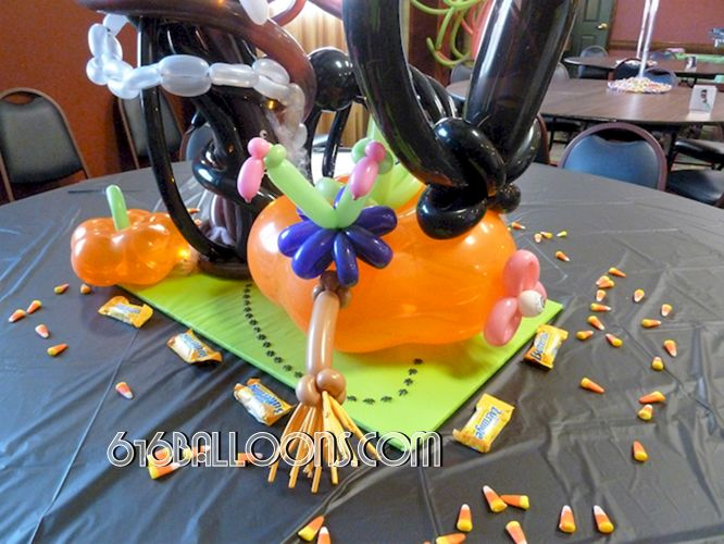 Halloween centerpiece witch crashed into pumpkin, flower eyeball balloon sculpture by 616Balloons.com Grand Rapids, Mi. Premium balloon art & decor. Corporate events, private parties..