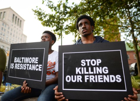 People gather to remember Freddie Gray and all victims of police violence during a rally outside city hall in Baltimore, Maryland.