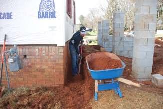 Jonathan digging below grade to hide all signs of old brick