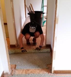 Jonathan rolling up carpet pad upstairs