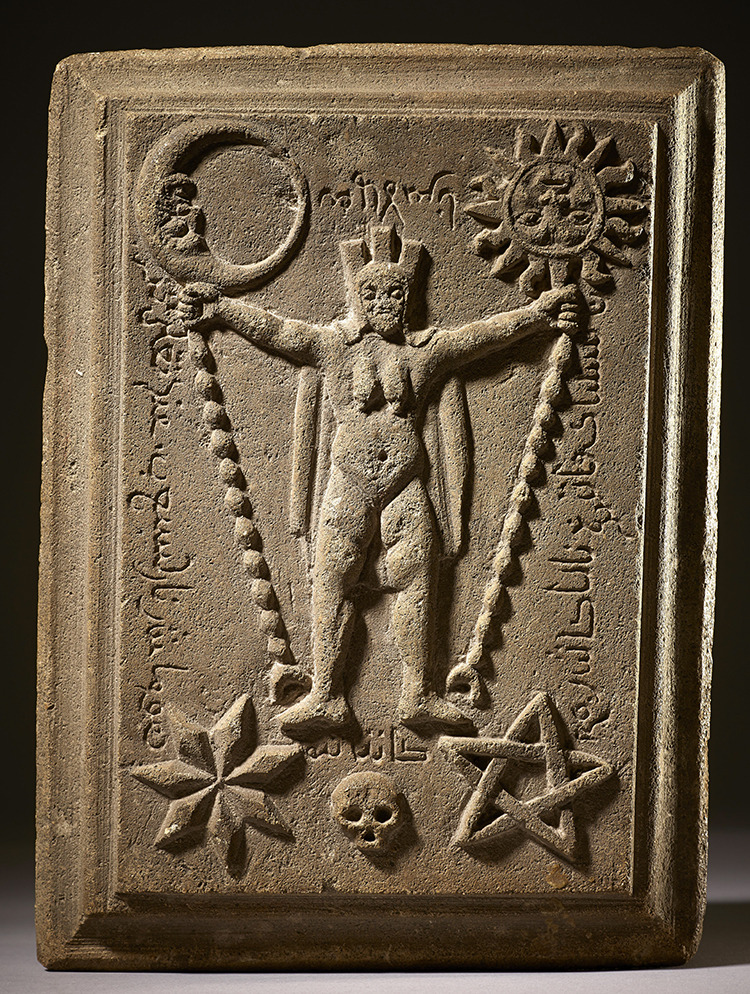 A stone slab featuring a bas relief of a naked, crowned woman with a cape, her arms outstretched to either side. In each hand she holds the top of a chain which is anchored by her feet. The chain in her right hand tethers the moon while the chain in her left hand tethers the sun. Both the sun and moon have faces, which are upside down from the viewer's perspective. Beneath her feet is a skull. To the left of the skull is a pentagram and to the right is a seven-pointed star. Pseudo-arabic script frames the woman.