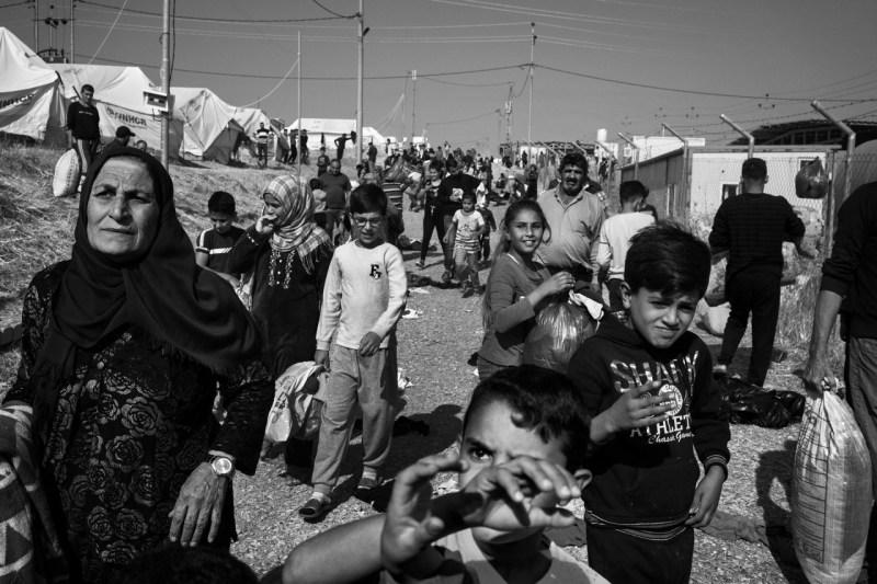 Сирийские курдские беженцы собираются, чтобы получить зимнюю одежду во время раздачи в лагере Бардараш 31 октября.